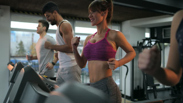 Group of young athletes running on a treadmilsl in a health club.