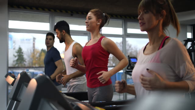 Group of young athletes running on treadmills in a health club.