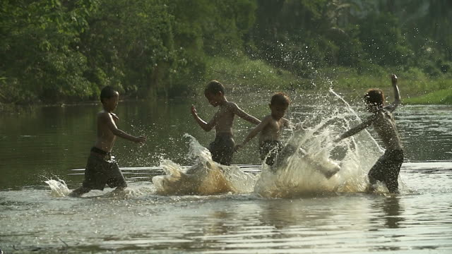 Group of young boy playing water splash with his buffalo on the field.Illustrate of a lifestyle of Asian developing countries.