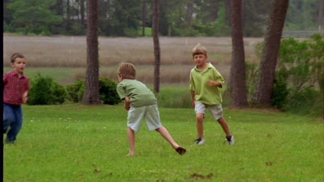 a group of young boys plays football in the backyard. - american football ball stock videos & royalty-free footage