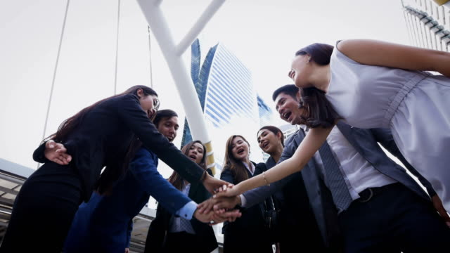 group of young business people joining hands together outside in modern city, success and team work concept - thai ethnicity stock videos & royalty-free footage