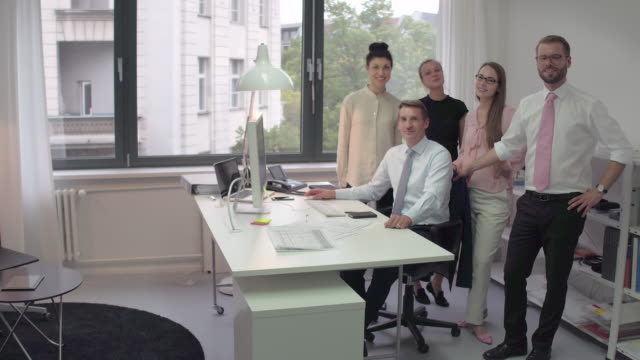 group of young business people standing behind elder manager looking into the camera smiling