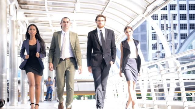 Groupe de jeunes gens d'affaires marche dehors sur la ville