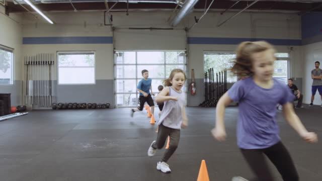 Grupp unga barn löper genom kottar