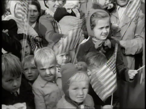 A group of young children wave US flags