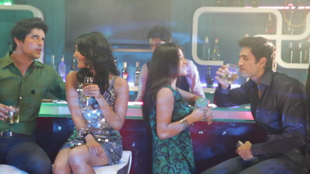 Group of young couple drinking alcohol at bar counter