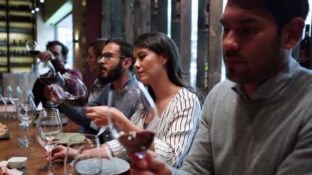 vidéos et rushes de groupe de jeunes couples à une classe de dégustation de vin apprenant et déplaçant le vin tout en regardant sa texture - goûter
