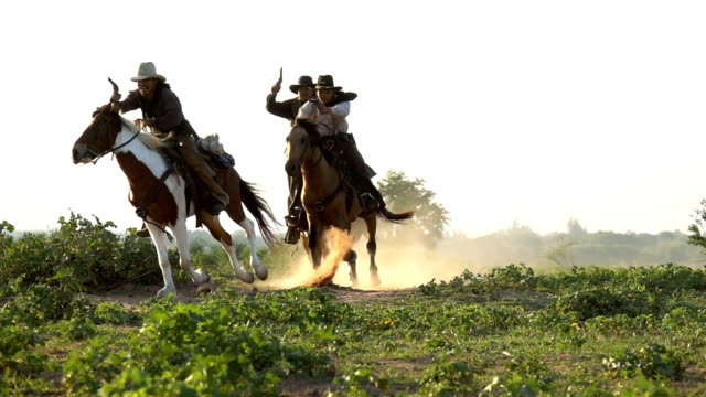 group of young cowboys holding gun and riding horse running in the meadow field - thai culture stock videos & royalty-free footage