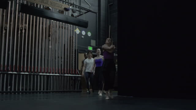 group of young dancers walking from back stage onto stage stretching arms. - entering stock videos & royalty-free footage