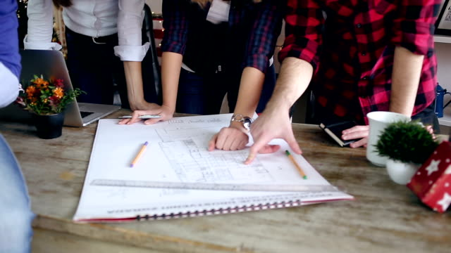 Group of young designers working together on blueprint