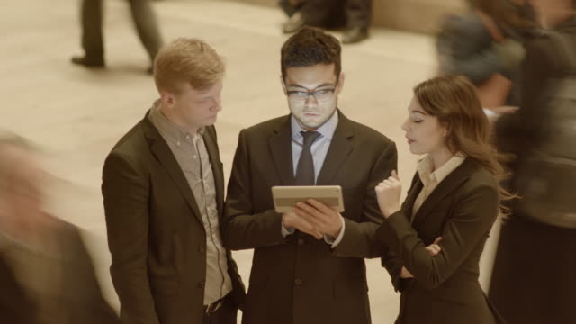 group of young diverse business professionals talking together looking at digital tablet computer