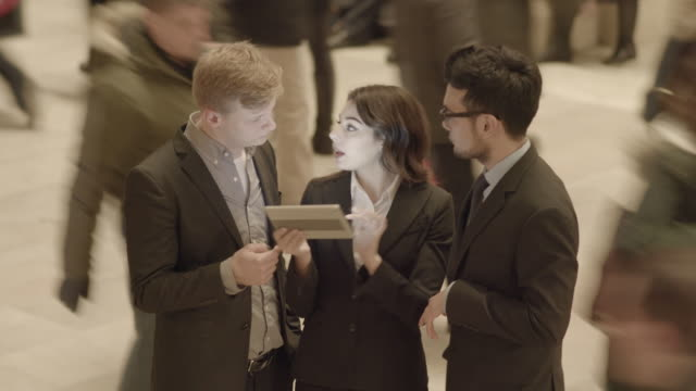 group of young diverse business professionals talking together looking at digital tablet computer - 隣り合わせ点の映像素材/bロール