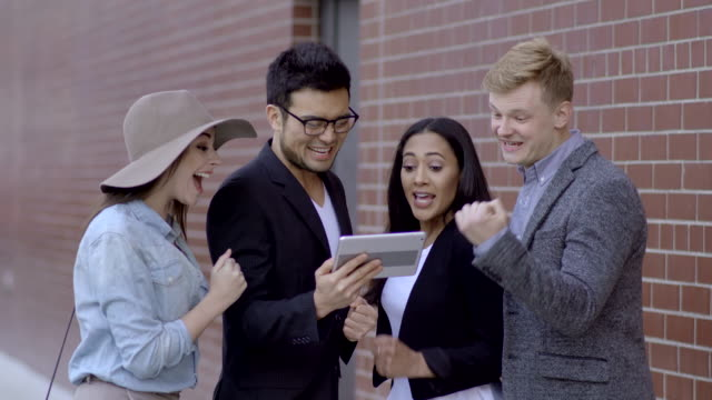 group of young diverse friends watching sports game on tablet computer outdoors cheering together after strike score. happy succesful business people portrait - technophile stock videos & royalty-free footage