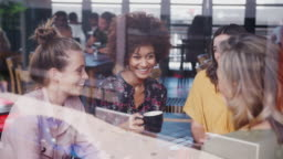 Group of young female friends meeting and sitting around table talking in cafe shot through window with reflections - shot in slow motion