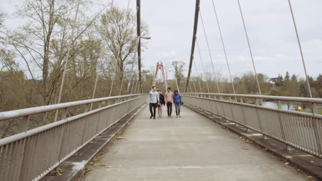 Group of young friends crossing a bridge