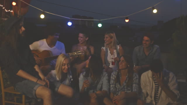 group of young friends relaxing on rooftop - patio stock videos & royalty-free footage