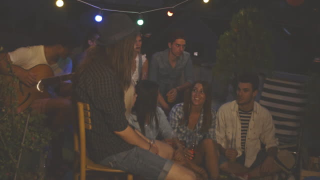 group of young friends relaxing on rooftop - acoustic guitar stock videos and b-roll footage