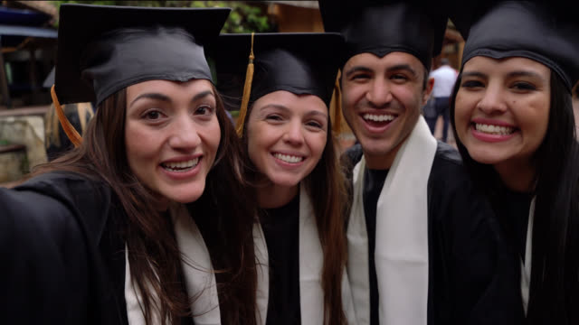 group of young friends taking a selfie making funny faces celebrating their graduation - graduation stock videos & royalty-free footage