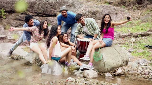 Group of young friends talking selfie picture with a mobile phone at riverbank, Shimla, Himachal Pradesh