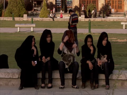 vídeos y material grabado en eventos de stock de group of young girls sitting, chatting in park, esfahan square, iran(sound available) - grupo mediano de objetos