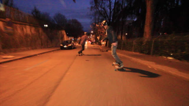 A group of young men longboard skateboarding downhill in a city at night.