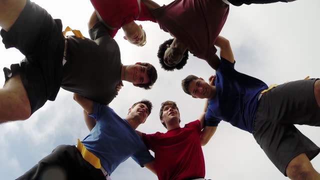 a group of young men playing flag football on the beach. - slow motion - low angle view stock-videos und b-roll-filmmaterial
