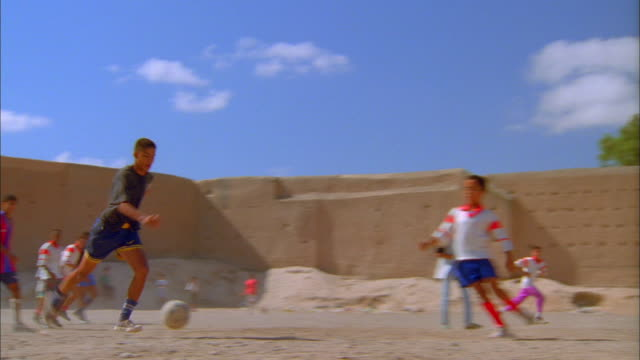 Group of young men playing soccer on dusty earthen pitch surrounded by high walls. Available in HD.