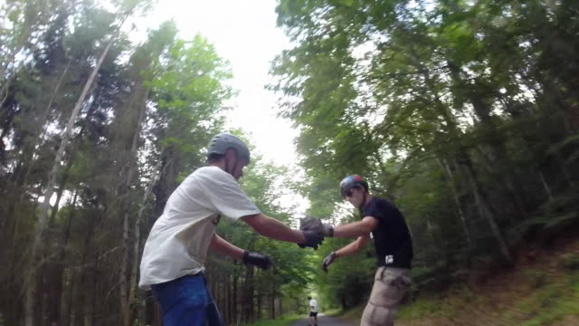 A group of young men ride their longboard skateboards downhill on a rural road give a fist bump.