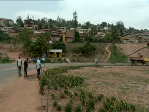 ws pan group of young men walking next to highway, with bridge that was damaged by shrapnel / kigali, rwanda - gemeinsam gehen stock-videos und b-roll-filmmaterial