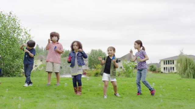 eine gruppe von jungen viertel kinder blasen blasen zusammen - seifenblasenring stock-videos und b-roll-filmmaterial