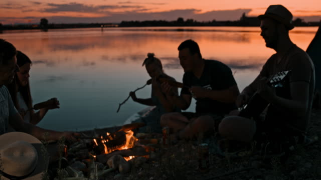 slo mo group of young people camping by the lake at dusk - evening meal stock videos & royalty-free footage