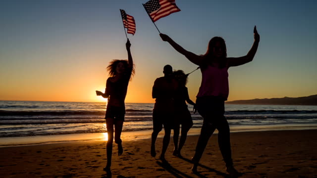group of young people celebrating on the beach - fourth of july stock videos & royalty-free footage