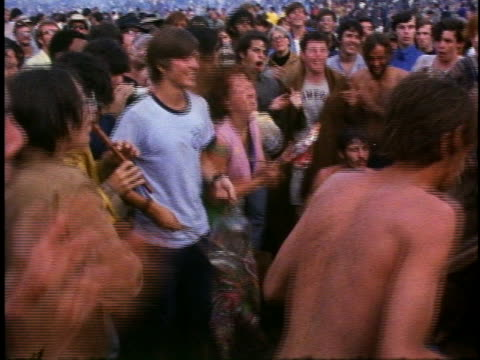 vidéos et rushes de group of young people chant, play bongos, and do the limbo at the woodstock music festival. - 1969