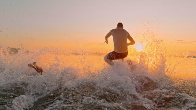 vídeos de stock e filmes b-roll de super slo mo group of young people dive into the lake - 20 24 anos