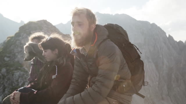 Group of young people hiking in the alps, sitting on a ridge