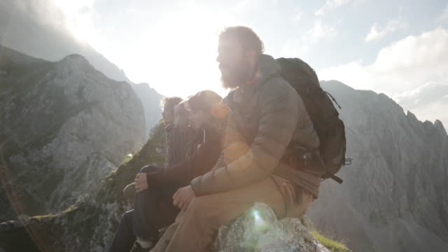 vídeos de stock, filmes e b-roll de group of young people hiking in the alps, sitting on a ridge - vida simples