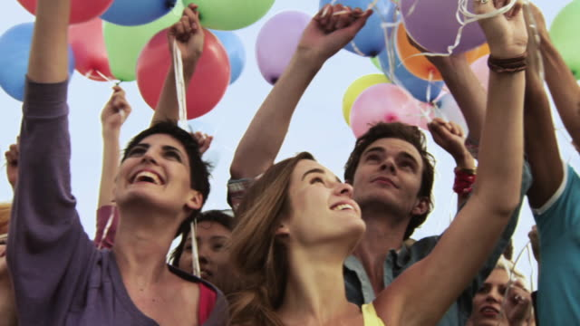 group of young people holding balloons - large group of people stock videos & royalty-free footage