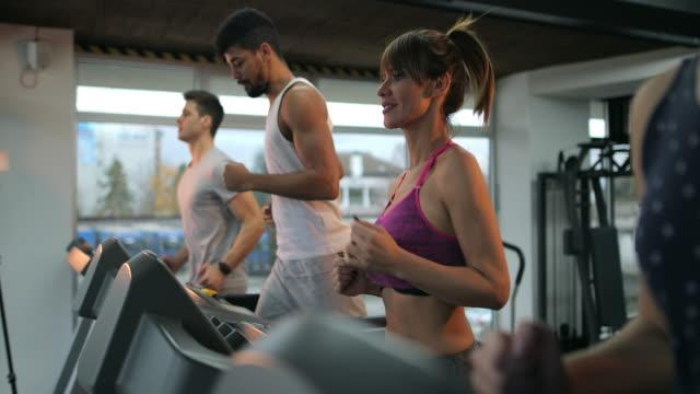 vídeos de stock, filmes e b-roll de grupo de jovens a correr em uma esteira em uma academia e se comunicando. - esteira rolante aparelho de musculação