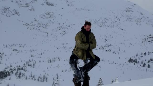 stockvideo's en b-roll-footage met group of young people performing acrobatic yoga in a mountain setting - armen over elkaar