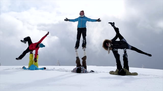 stockvideo's en b-roll-footage met group of young people performing acrobatic yoga in a mountain setting - acrobatiek