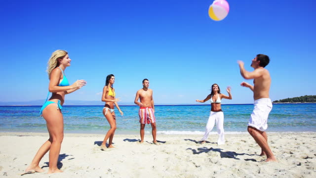 Group of young people playing ball on the beach.