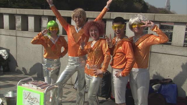 ms group of young people posing in orange space outfits, tokyo, japan - 扮装点の映像素材/bロール