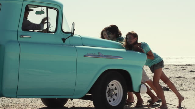 ms pan group of young people pushing vintage pickup truck out of beach / cape town, western cape, south africa - spingere video stock e b–roll