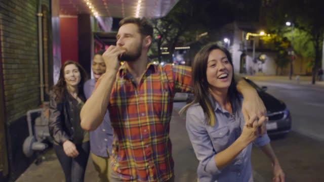 group of young people run into friends walking through downtown austin, texas at night - hometown bildbanksvideor och videomaterial från bakom kulisserna