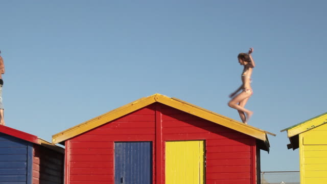 MS Group of young people running across beach hut's rooftop / Cape Town, Western Cape, South Africa