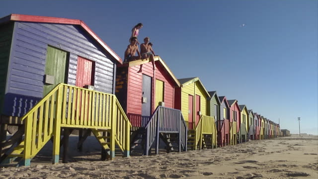 WS Group of young people sitting on beach hut's roof, two men jumping of roof / Cape Town, Western Cape, South Africa
