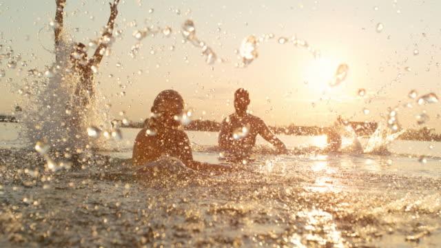 stockvideo's en b-roll-footage met super slo mo groep jonge mensen spetteren water in het meer - verfrissing
