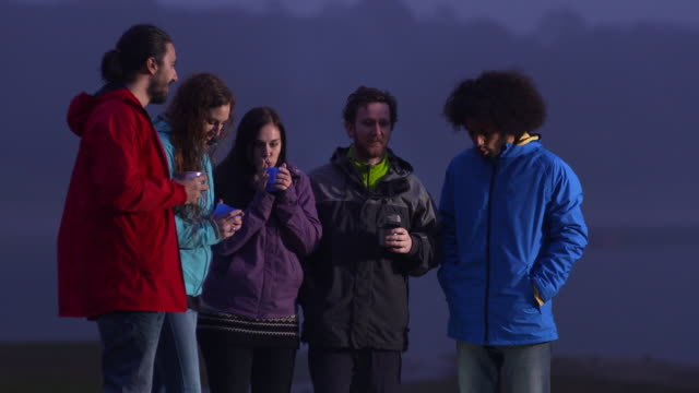 stockvideo's en b-roll-footage met ms group of young people standing by side of lake at dusk drinking and chatting - duurzaam toerisme