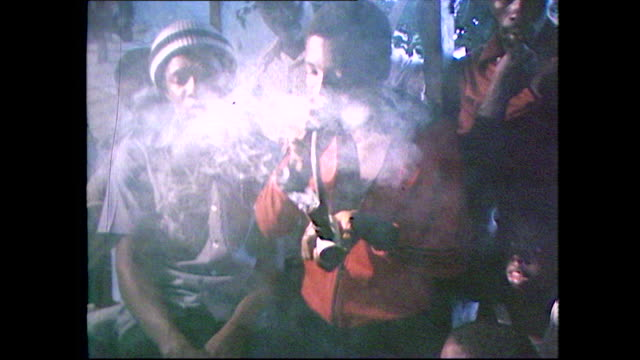 a group of young rastafarian men in jamaica smoke marijuana from a large pipe one man lights the pipe and another inhales and exhales clouds of smoke... - adults only videos stock videos & royalty-free footage