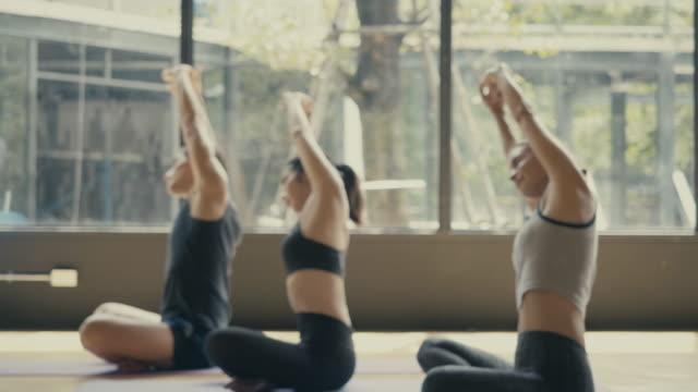 gruppe junger sportler, die yoga-unterricht praktizieren - sportkleidung stock-videos und b-roll-filmmaterial